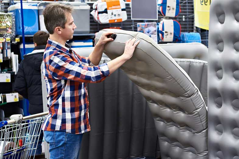 Man Choosing an Air Mattress at a Store