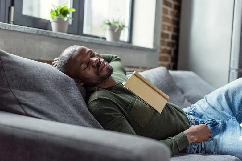Man With Book Sleeping on Couch at Home