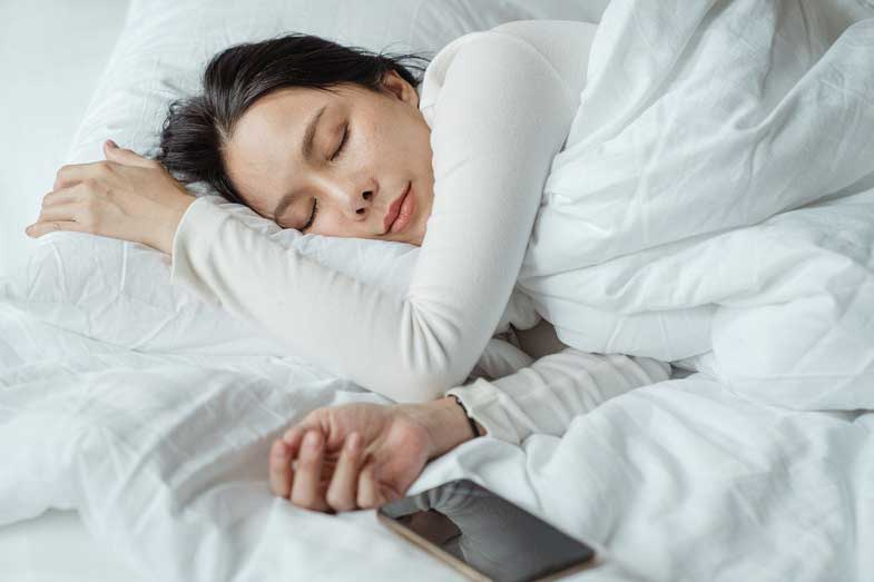 Woman Sleeping Next to Cell Phone