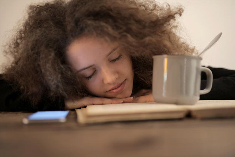 Woman Sleeping on Table Next to Cup