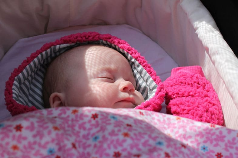 A Baby Sleeping In Hooded Pajamas