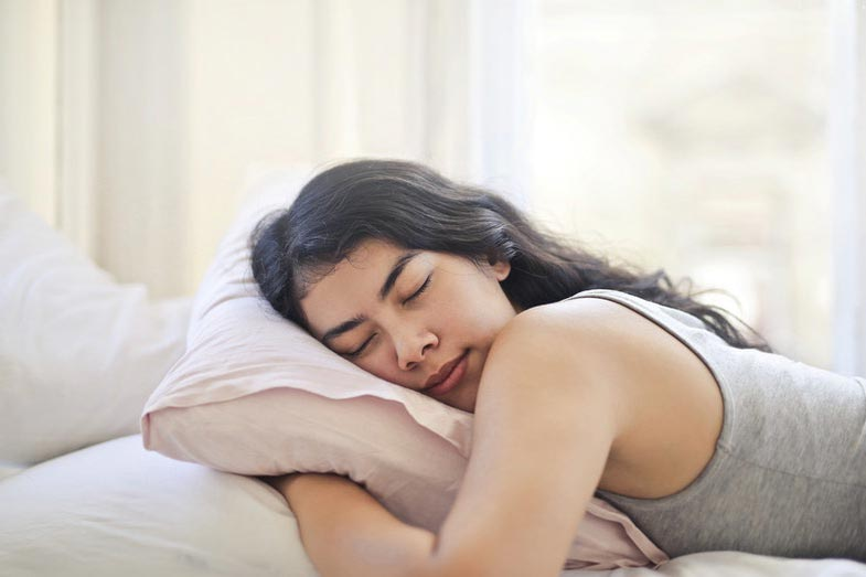 Woman in Gray Tank Top Sleeping on Stomach in Bed