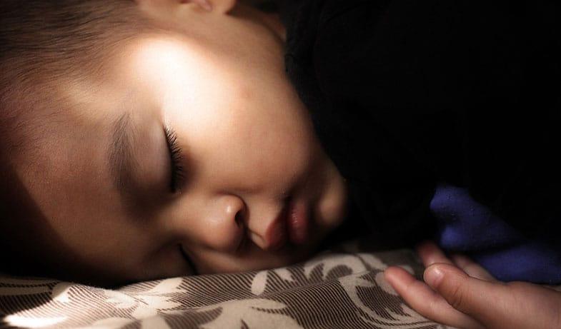 Child Sleeping Next to Night Light
