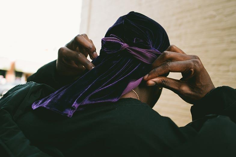 Man Adjusting His Purple Velvet Durag