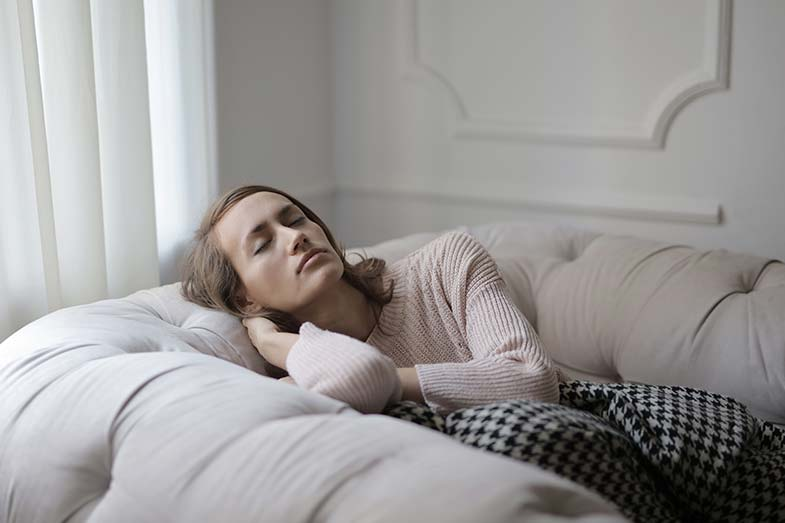 Girl in White Sweater Sleeping on Couch