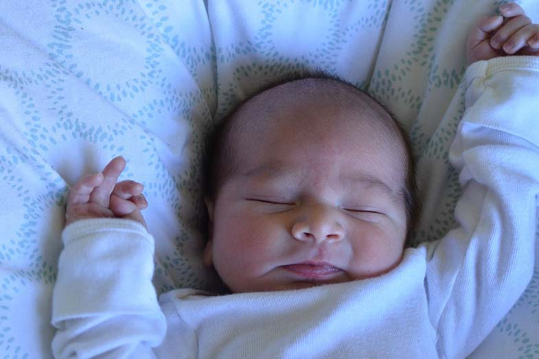 Newborn Baby Sleeping with Arms Up