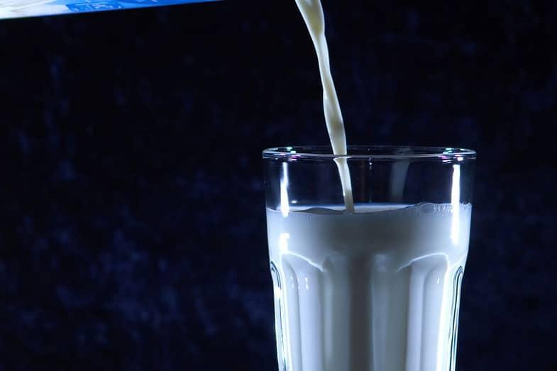 Carton of Milk Pouring Into Glass
