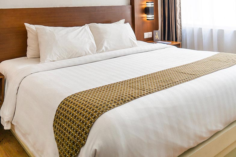 Large, Wide, White Bed With Wooden Headboard