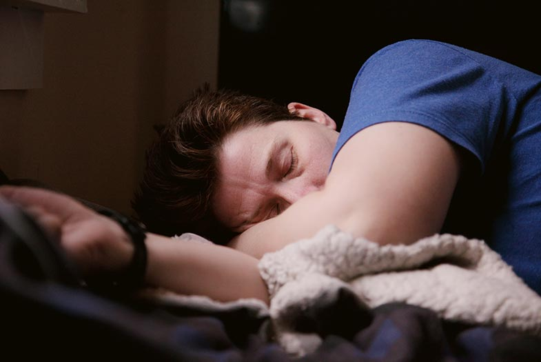 Man in Blue Shirt Sleeping on Side