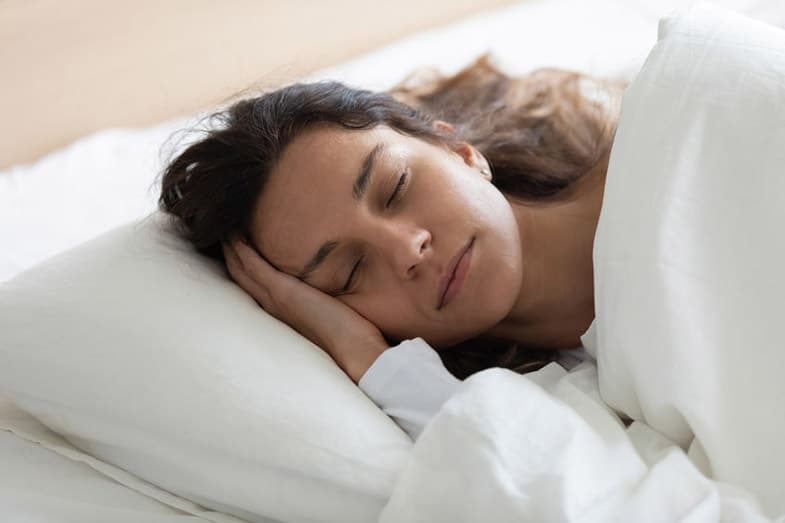 Woman Lying in Bed Sleeping on Side