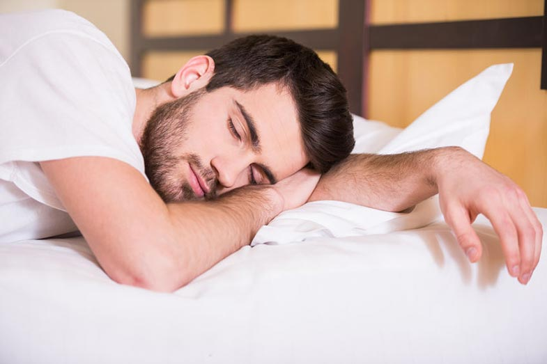Close-up of Young Man Sleeping in a Bed