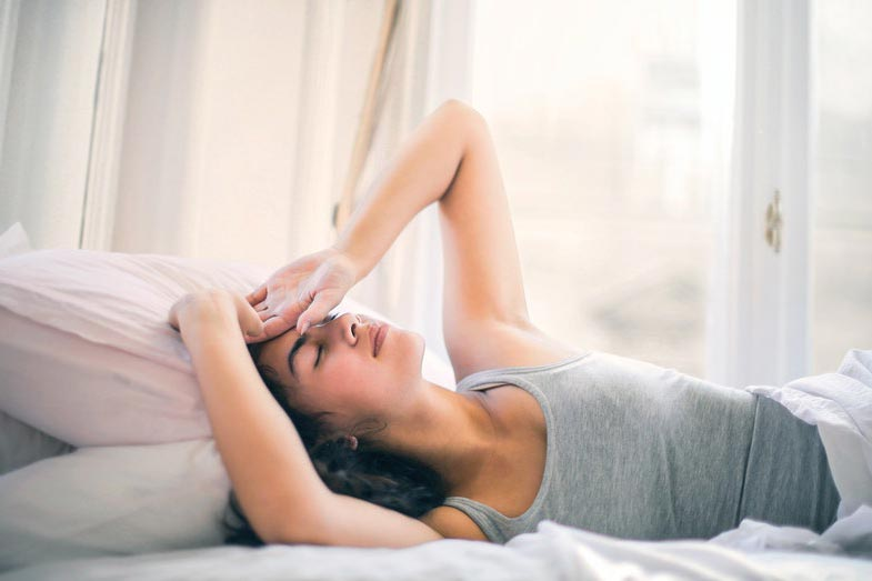 Woman in Gray Tank Top Sleeping in Bed With Hands on Head