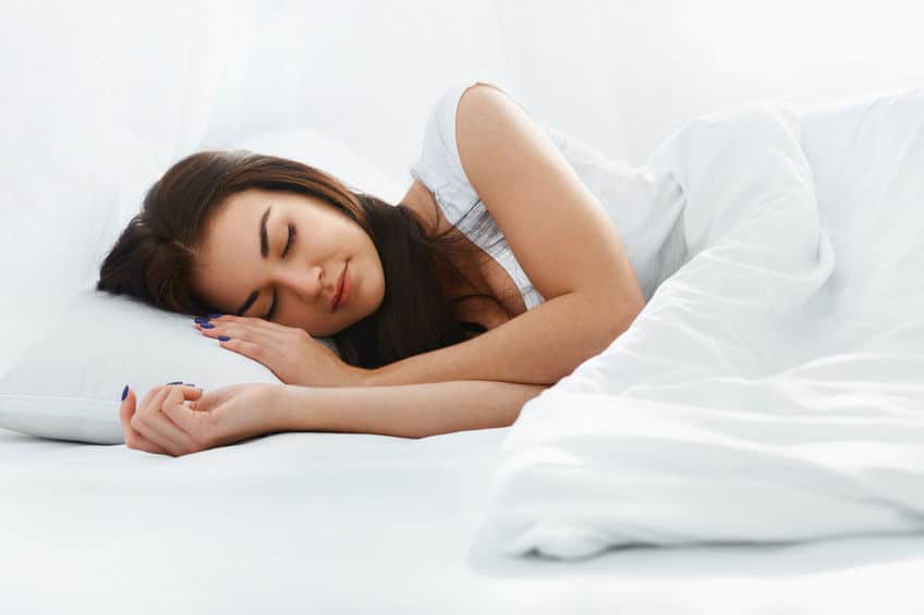 Girl Sleeping on Pillow in Comfortable Bed