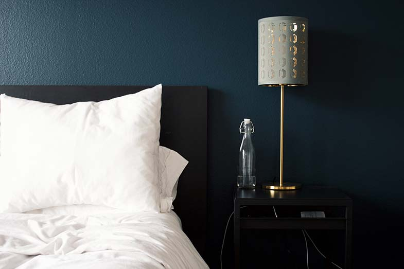 White Bed Next to Table and Lamp