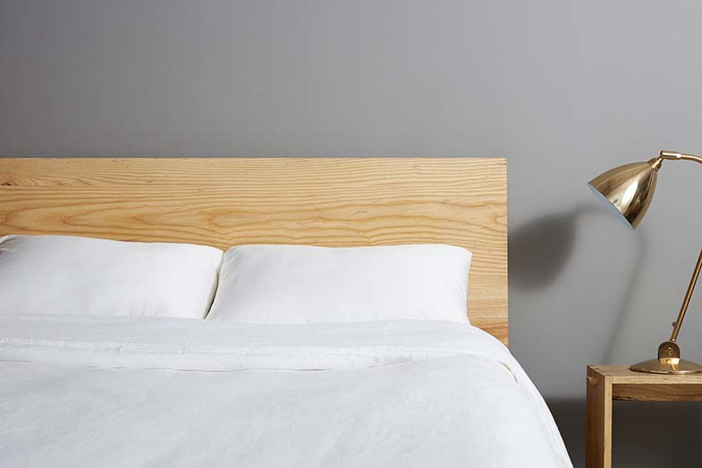 White Bed with Wooden Headboard Next to Lamp