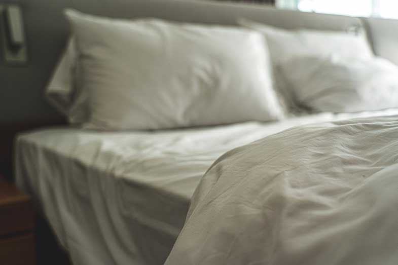 White Bed Sheets, Pillows, and Blanket