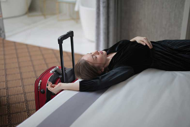 Woman Lying on Hotel Bed Next to Suitcase