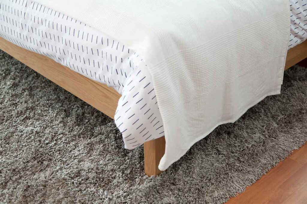 Bedding Frame with White Blanket and Mattress
