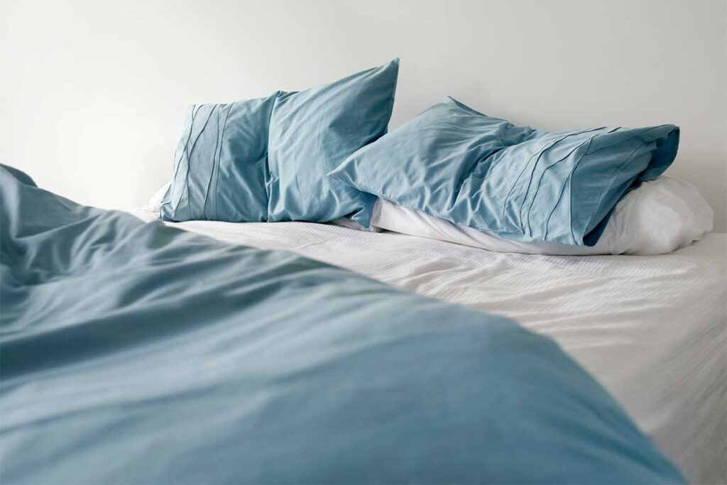 Unmade Bed with Blue Pillows